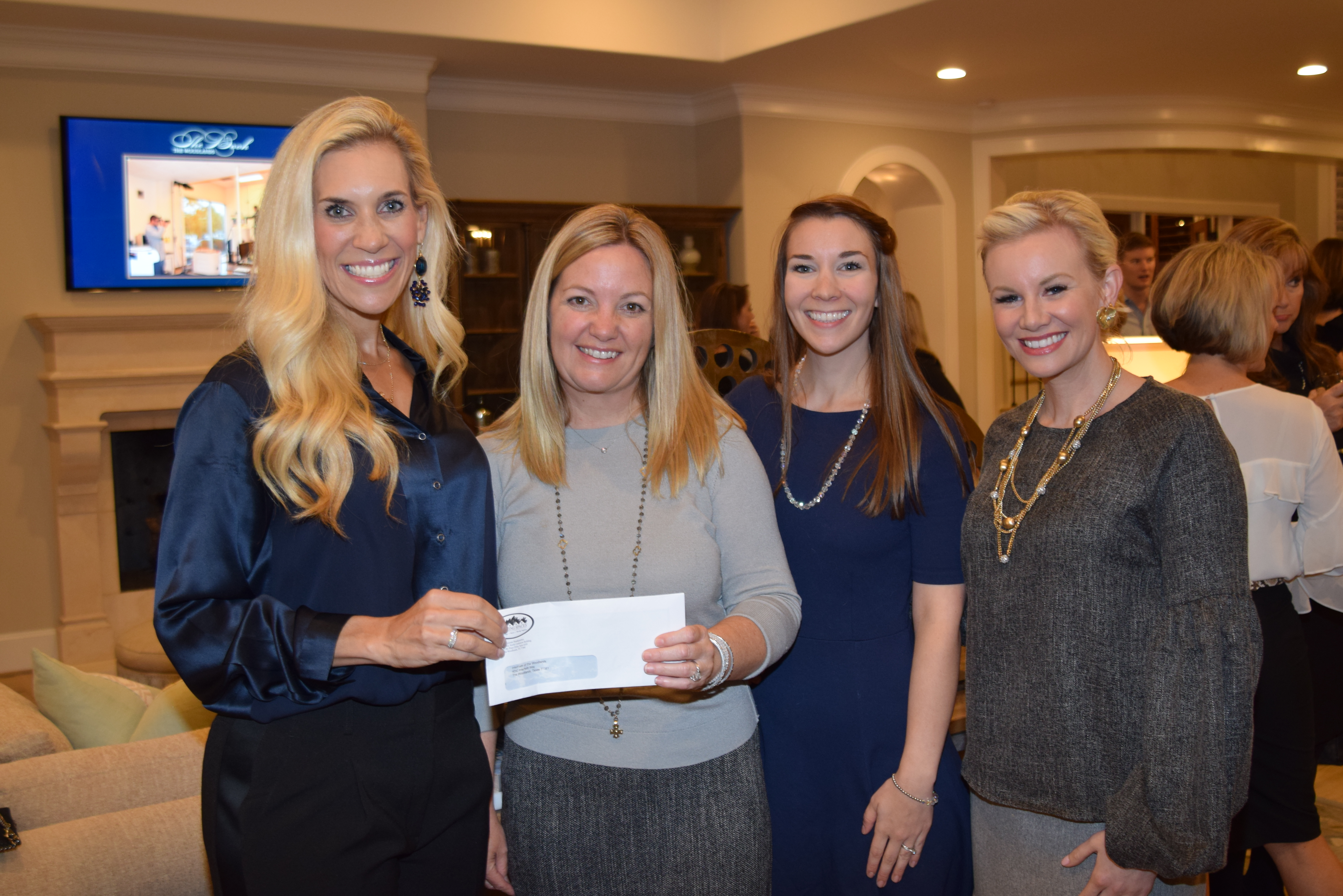 Amazing Spaces presents check to Interfaith of The Woodlands