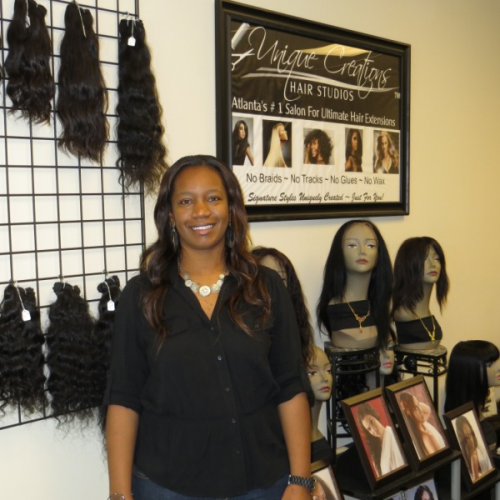 Salon Owner in front of display with Wigs in Atlanta for Can'