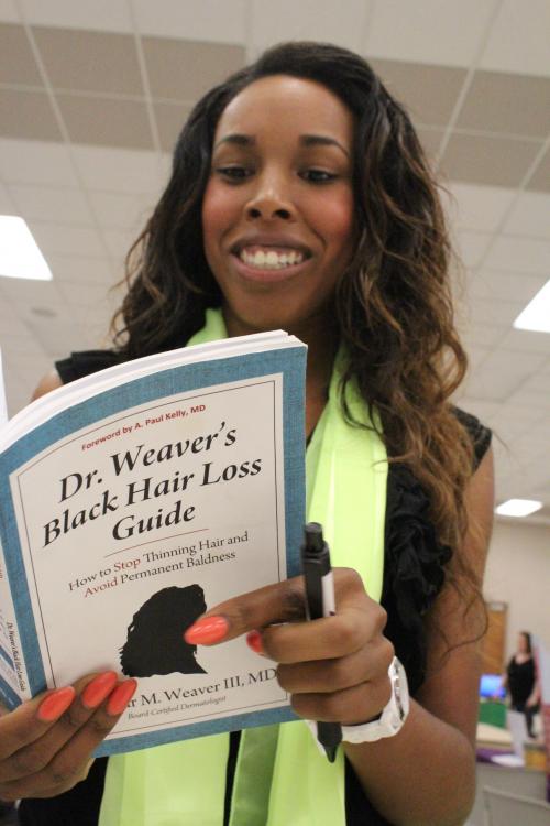 Octavia reading Dr. Seymour Weaver's Black Hair Loss Guide'