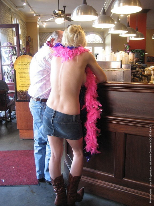 Topless woman in a New Orleans coffee shop during Mardi Gras'